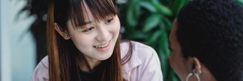 asian woman smiles talking to college