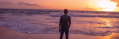 man facing backward stands hand in pocket on beach in beautiful sunset sky