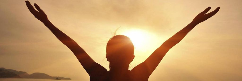 woman raises hands feeling grateful in sunny sky