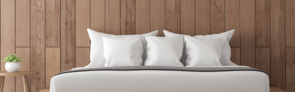 nice decorated bedroom white pillows folded blanket beside side table plant pot wood wall