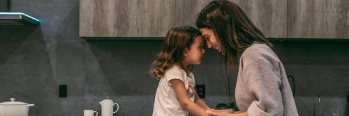 woman stands head to head with adorable daughter looking smiling in kitchen