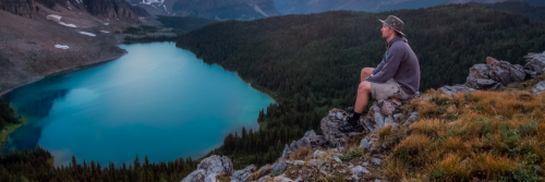 man sits on rock on top of mountain beside lake