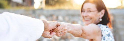 elderly woman happily smiles holding husband hand