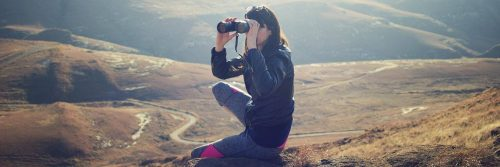 woman sits on rock seeing mountain world through binocular vision