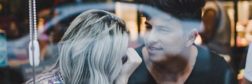 couple sits in coffee shop looking at talking to each other