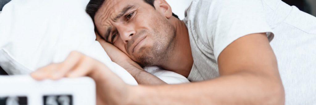 man lies on bed holding clock having insomnia problem