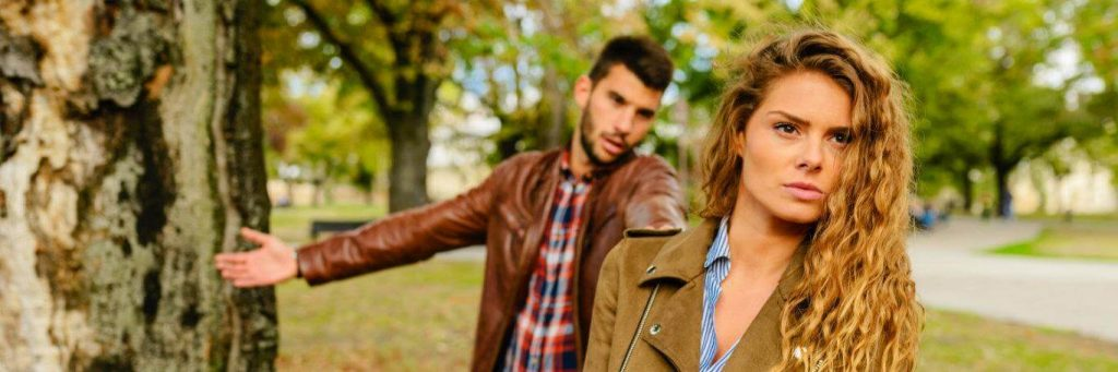 couple haves conflict in public park man trying to explain while woman angrily waking away