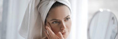 woman covering hair with white towel applies skin care