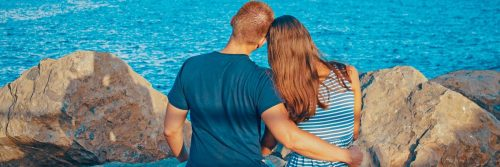 couple facing backward sits on rock side by side hugging looking at blue ocean