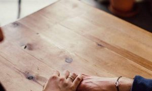 woman holds man hand listening to him talking