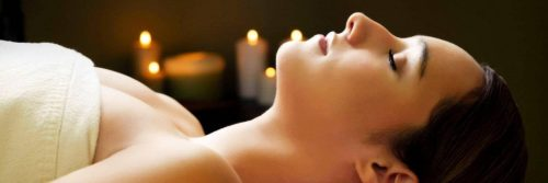 woman lies down eyes closed covering body with towel beside candles