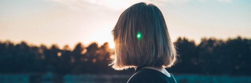 short hair woman facing backward stands looking at sunny sky