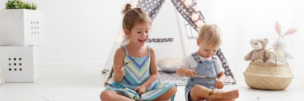 two adorable naughty children sits in living room painting on hands beside toys teddy bear