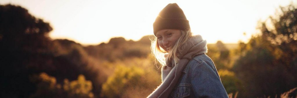 woman wearing black hat purple scarf stands in field happily smiling in sunny sky