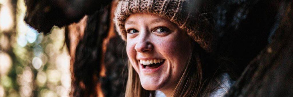 woman wearing hat smiles