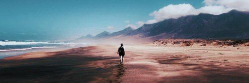 person walks on sand beside blue ocean mountain blue cloudy sky