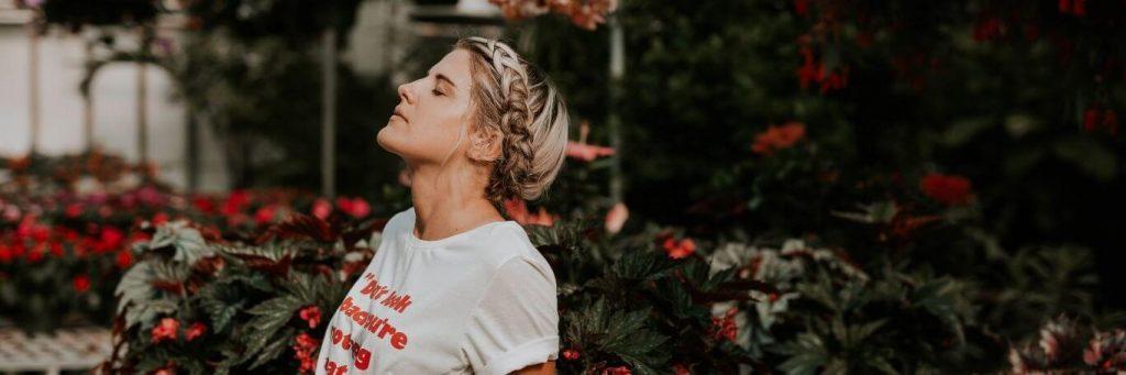 woman stands beside red flower garden closing eyes breathing