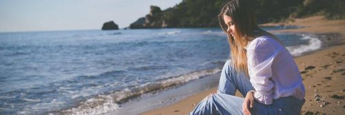 woman sits on sand beside beach feeling sad after relationship breakup