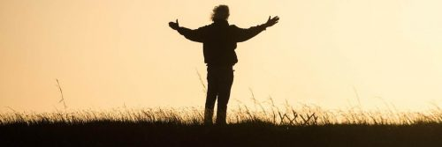 man stands facing backward on field gratitude life in red clear sky