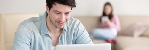 man smiles studying laptop while woman sitting using mobile phone on white couch