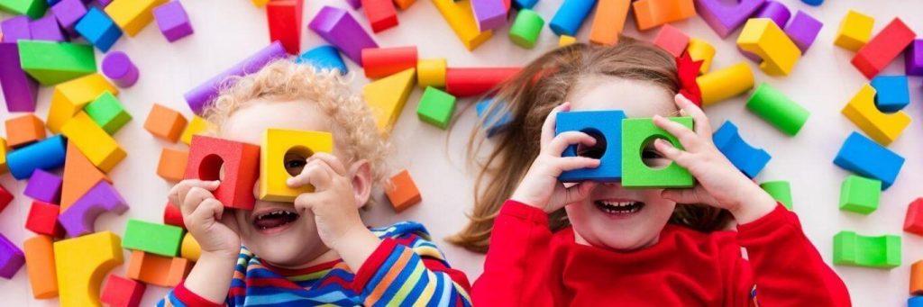 two adorable children play toys legos