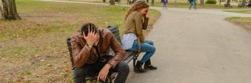 couple sits on bench in park head on face having conflict not talking to each other
