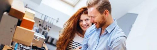 couple stands in kitchen happily laughing