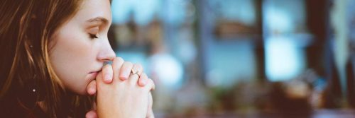 woman eyes closed sits holding hands thinking praying