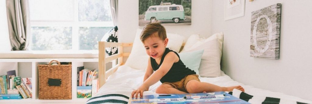 little adorable boy sits on bed excitedly read kids children book in tidy cozy bedroom