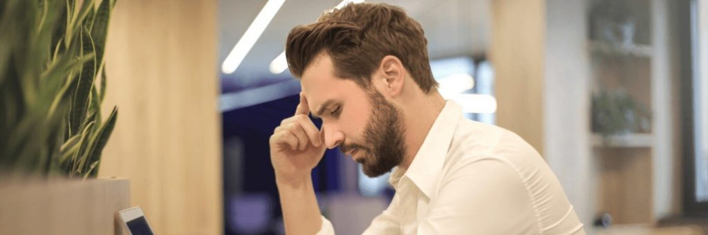 man sits in library hand in forehead thinking looking at laptop