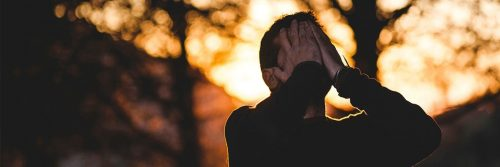 man stands hands in face feeling sad shameful in forest in sunny sky