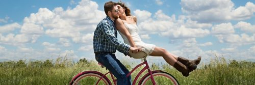 couple happily ride along green field while woman sits in front kissing partner
