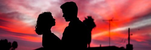 couple shadow hugging looking at each other in dark red sky