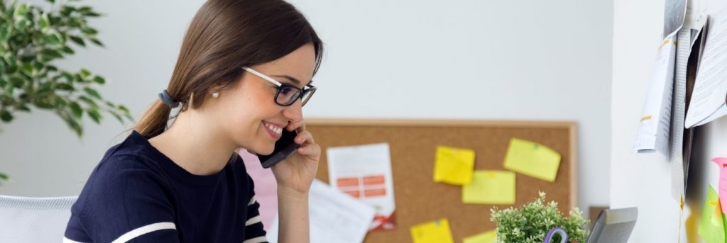 woman happily smiles answering phone while sitting in office
