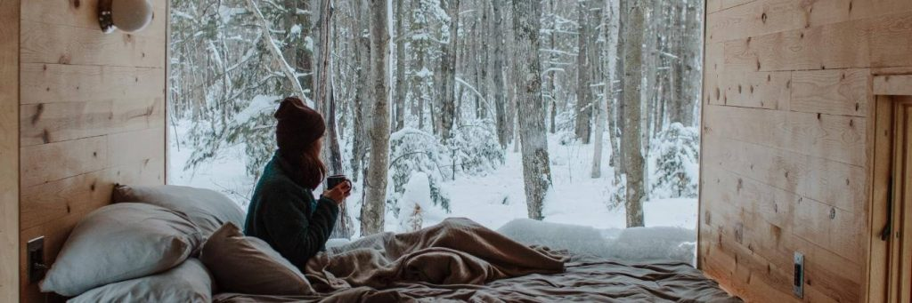 woman holding mug sits in house beside pillows watching snow