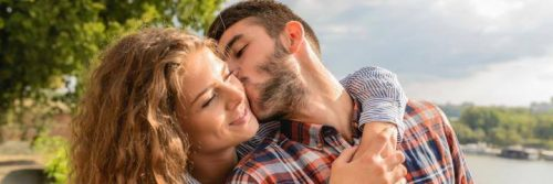 man kisses girlfriend on cheek while woman hugging from behind
