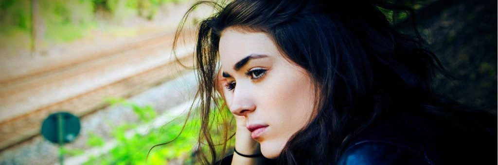 woman sadly wistful eyes sitting worrying about life
