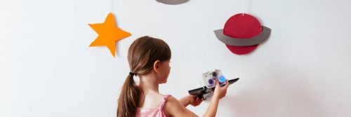 little girl plays toy beside white wall decorated with universe symbols