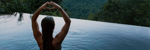 woman stands in swimming pool two hands making heart shape