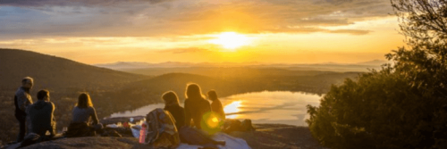 group of people sits on mountain top enjoying picnic watching sunset