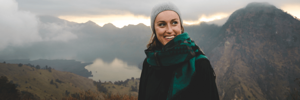 woman wearing winter hat scarf stands smiling on top of mountain in foggy weather
