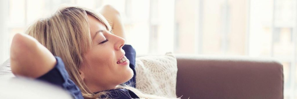 woman hands over head lying on couch smiling