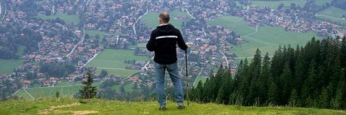 elderly stands on mountain top holding stick looking at countryside