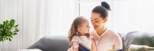 woman sits on couch smiling reading book for little adorable daughter in living room