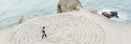 man walking within maze on rock beside beach