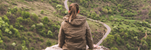 woman facing backward stands alone on rock sightseeing