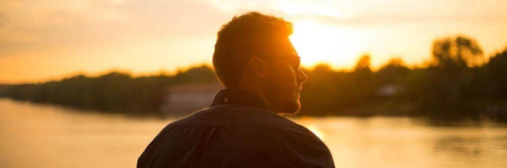 man wearing sunglasses facing backward stands beside ocean looking at sunset