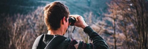 man looking forest through binocular vision
