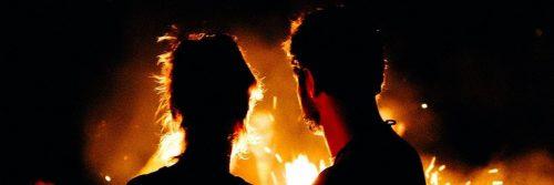 man facing backward looks at girlfriend near flame