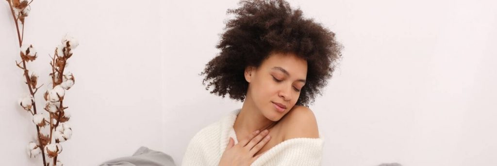 curly black hair woman closed eyes hand on chest feeling loved herself